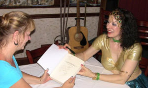 Alay'nya showing dancer a coy of Unveiling: The Inner Journey, at the book launch party in Reston, VA, in 2011.